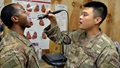 Air Force Staff Sgt. Danny Lim practices conducting a throat examination on Army Sgt. Harvey Drayton at Chabelley Airfield, Djibouti. Drayton and Lim were introduced to the Telehealth In A Bag system during a recent visit that included personnel from Regional Health Command Europe's virtual health team. (U.S. Army photo by Russell Toof)
