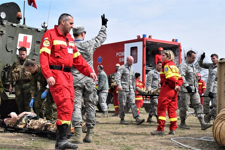 Civilian first responders from Romania participate along with Airmen from the 86th Medical Group, Ramstein Air Base, Germany, in a multinational medical exercise drill during Vigorous Warrior 19, Cincu Military Base, Romania. Vigorous Warrior 19 is NATO's largest military medical exercise, uniting more than 2,500 participants from 39 countries to exercise experimental doctrinal concepts and test their medical assets together in a dynamic, multinational environment. (U.S. Air Force photo by 1st Lt. Andrew Layton)