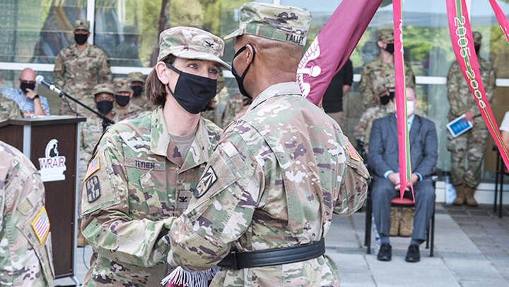 Two soldiers, wearing masks, passing a flag