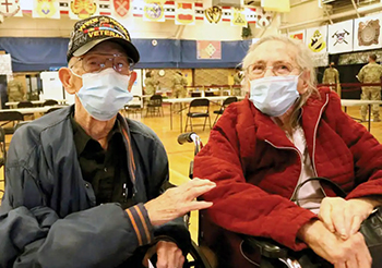 Retired veteran and his wife wearing face mask waiting to receive the COVID-19 vaccine