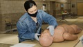 Medical personnel, wearing a mask, practicing skills on a dummy