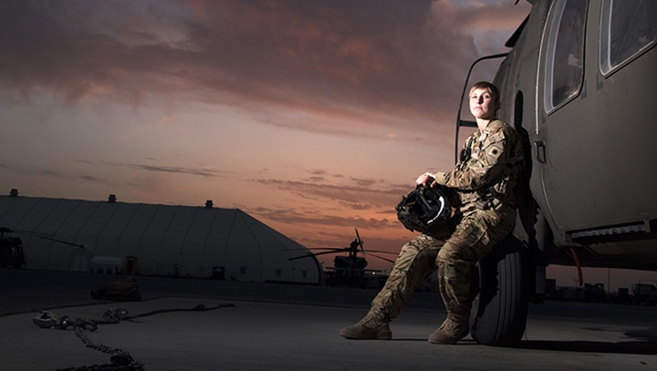 Female soldier, leaning against a military vehicle, at sunset