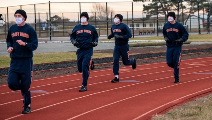 Four military personnel, wearing masks, running on a track