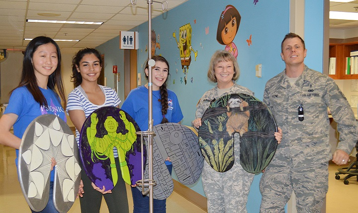 "Lillian Sun, Amaya Mali and Sophie Rosenberg, students with the Westlake Robotics Club, display a few of their donated IV pole ""lilypads"" with the help of Army Col. Elizabeth Murray and Air Force Master Sgt. Sean Keene in an inpatient pediatric ward. The Robotics Club students constructed and donated 10 lily pads to pediatric patients at Brooke Army Medical Center. ( U.S. Army photo by Elaine Sanchez)"