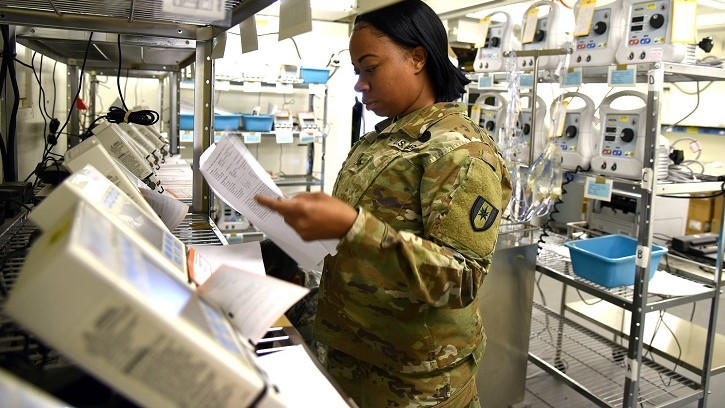 Soldier looking at medical equipment on shelves