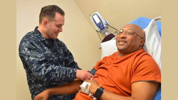 "Hospitalman Payton Dupuis, a native of Mill City, Oregon, checks veteran Joseph Levette's blood pressure at Naval Hospital Jacksonville's internal medicine clinic. ""Men's health is a vital part of the mission,"" stated Dupuis. ""We need a healthy workforce to succeed."" (U.S. Navy photo by Jacob Sippel)"