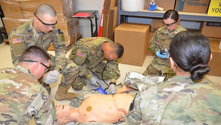 "A team of combat medic trainees attend to a ""patient"" in the EMT warehouse lab.  Students engage in various scenarios in the newly designed EMT simulation labs that resemble real environments that expose students to lifelike patient encounters. (U.S. Army photo by Lisa Braun)"