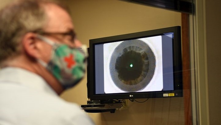 Image of Mr. McCaffery looking at a monitor with an eye on it