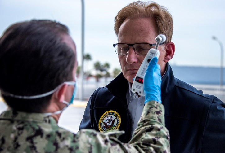 Image of man getting his temperature taken by service member wearing a mask.