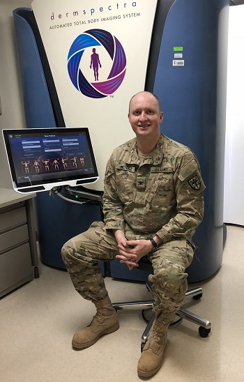 Army Colonel Jon Meyerle, sits in front of a total body digital skin imaging system. The system takes standardized, full-body photographs of patients to help track changes in skin conditions over time. Images can be assessed by a patient's medical provider at a later date. (Courtesy Photo)