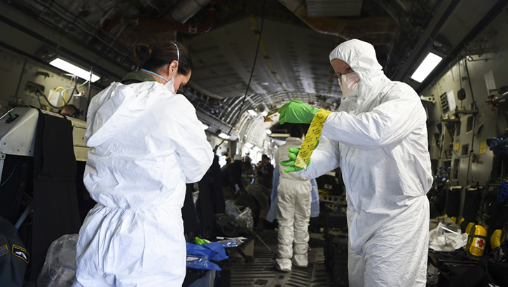 Airmen assist one another in donning their personal protective equipment, while on-board an Air Force C-17 Globemaster III during transportation isolation system training at Joint Base Charleston, South Carolina. Engineered and implemented after the Ebola virus outbreak in 2014, the TIS is an enclosure the Department of Defense can use to safely transport patients with diseases like novel coronavirus. (U.S. Air Force photo by Senior Airman Cody R. Miller)