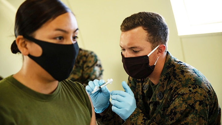 Healthcare worker giving vaccine to soldier; both wearing masks