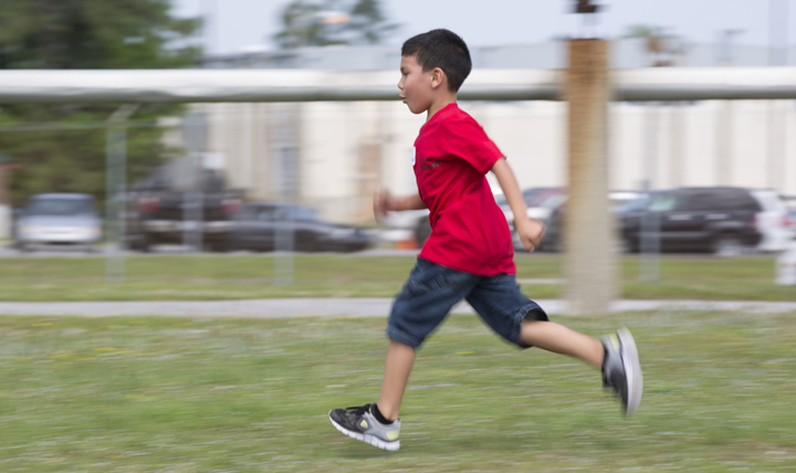 "Christian Macias runs in a combat fitness test modified for children at a ""bring your child to work day"" event at Marine Corps Air Station Cherry Point, North Carolina. (U.S. Marine Corp photo by Sgt. N.W. Huertas)"
