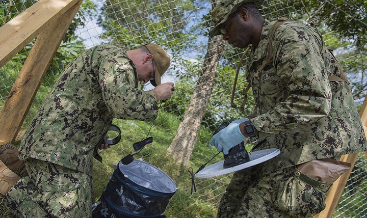 Navy Lt. Marcus McDonough and Navy Hospital Corpsman 1st Class Adrian Weldon, assigned to Navy Environmental and Preventative Medicine Unit TWO, prepare a BG-Sentinel mosquito trap outside the Franklin D. Roosevelt School during Continuing Promise 2018.(U.S. Navy photo by Mass Communication Specialist 2nd Class Brianna K. Green)