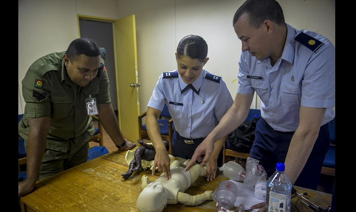 Sergeant Natoga Anitelu, left, a medical services technician with Fiji's military forces, discusses the best ways to clear an infant's airway with U.S. Air Force Capt. (Dr.) Paola Rosa, center, and U.S. Air Force Maj. (Dr.) Scott Stewart, right, during a subject-matter-expert exchange as part of exercise Pacific Angel 17-3 at a health care center in Ba, Fiji. (Air Force photo by Capt. Samantha Morrison)