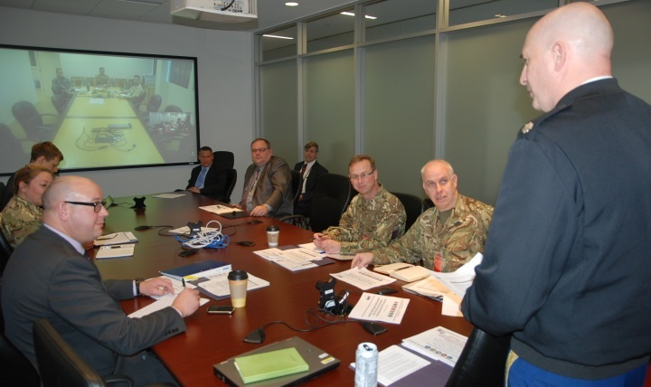 Army Lt. Col. Mark Mellott with the Defense Health Agency's health IT division  (standing) addresses members of a British military delegation and members of the Military Health System's Health IT and innovation leadership.